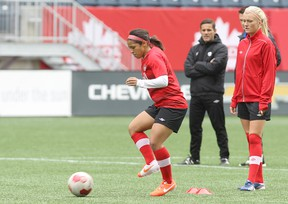 National women's soccer team midfielder Desiree Scott of Winnipeg  goes through a drill as midfielder Kalyn Kyle (right) looks on during practice at Investors Group Field in Winnipeg, Man., on Wed., May 7, 2014. Canada faces the United States in a friendly on Thu., May 8. Kevin King/Winnipeg Sun/QMI Agency