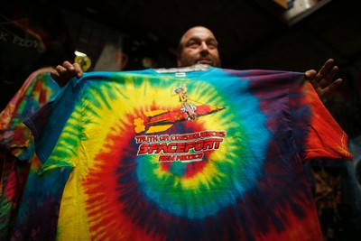 Jeff Dukatt, 59, displays a tie-dyed spaceport T-shirt he made at his store in Truth or Consequences, New Mexico May 1, 2014.  The world's first purpose-built commercial space base and soon-to-be site of the first space flights with Sir Richard Branson's Virgin Galactic is near the town of Truth or Consequences in New Mexico. The inaugural flight into suborbital space should happen later this year and the first astronauts, who have made reservations and paid $250,000 for the flight, should follow a month later. While it's not clear what the economic impact will be, many agree that Spaceport America should inject new energy into the town. Picture taken May 1, 2014.      REUTERS/Lucy Nicholson