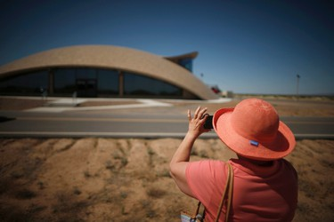 A tourist photographs Spaceport Operations Center at Spaceport America near Truth or Consequences, New Mexico May 2, 2014. The world's first purpose-built commercial space base and soon-to-be site of the first space flights with Sir Richard Branson's Virgin Galactic is near the town of Truth or Consequences in New Mexico. The inaugural flight into suborbital space should happen later this year and the first astronauts, who have made reservations and paid $250,000 for the flight, should follow a month later. While it's not clear what the economic impact will be, many agree that Spaceport America should inject new energy into the town. Picture taken May 2, 2014.      REUTERS/Lucy Nicholson