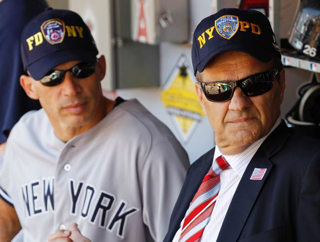New York Yankees manager Joe Girardi stands with former New York Yankees manager Joe Torre in the dugout as they wear FDNY and NYPD baseball caps on the 10th anniversary of the 9/11 attacks on September 11, 2011 (REUTERS/Danny Moloshok)