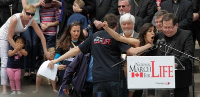 A topless pro-choice protester tries to disrupt Gerald Lacroix, Archbishop of Quebec, during Thursday's National March for Life anti-abortion rally. Tens of thousands of people gathered for the march which started on Parliament Hill in Ottawa.  (Tony Caldwell/QMI Agency)