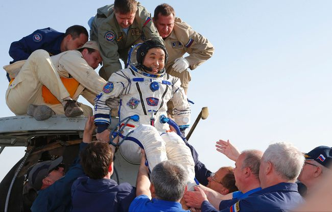 The International Space Station (ISS) crew member Japanese astronaut Koichi Wakata is helped by ground search and rescue personnel after landing south-east of the town of Dzhezkazgan in central Kazakhstan, May 14, 2014. (REUTERS/Dmitry Lovetsky/Pool)