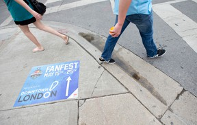Pedestrians walk past a sign on the sidewalk directing foot traffic to the Memorial Cup Fan Fest in Jubilee Square, between Budweiser Gardens and the Covent Garden Market. (CRAIG GLOVER/The London Free Press)
