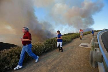 After climbing a hillside to view the so-called Poinsettia Fire, residents are evacuated by police as yet another wildfire near San Diego moves up a hillside near San Marcos, California May 14, 2014. At least two structures burned to the ground and some 15,000 homes and businesses were told to evacuate on Wednesday as the wind-lashed Poinsettia wildfire roared out of control in the heart of a Southern California coastal community. The blaze, which erupted shortly before 11 a.m. in Carlsbad, some 25 miles north of San Diego, quickly became the most pressing battle for crews fighting flames across the region amid soaring temperatures and hot Santa Ana winds.   REUTERS/Mike Blake