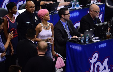 Rihanna caused a stir while watching a basketball game in Los Angeles on Thursday by sitting courtside in a pink wig and a revealing top.