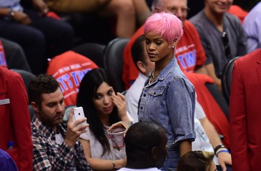 Pop star Rihanna leaves the court drink in hand during the Los Angeles Clippers v. Oklahoma City Thunder game on May 15, 2014 at Staples Center in Los Angeles, California, of their NBA playoffs round two series. AFP PHOTO/Frederic J. BROWN