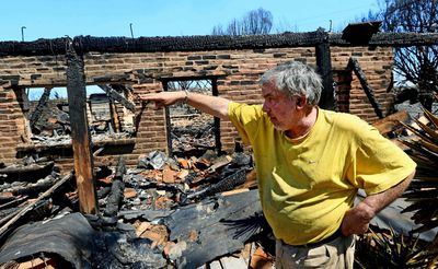 Greg Saska surveys the damage to his home after it was destroyed during the Poinsettia Fire in Carlsbad, California May 15, 2014.  Whipped by the wind, flames swept over the parched land close to homes and roads in nine fires across the county, with black smoke filling the sky as California entered the height of wildfire season in the midst of one of the state's worst droughts. No major injuries were reported.  REUTERS/Sandy Huffaker  (UNITED STATES - Tags: ENVIRONMENT DISASTER)