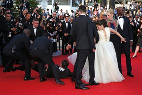 """A man is arrested by security as he tries to slip under the dress of actress America Ferrera (3rdR) as she poses on the red carpet arriving for the screening of the film """"How to Train Your Dragon 2"""" out of competition at the 67th Cannes Film Festival in Cannes May 16, 2014. From R, Cast members Djimon Hounsou, Cate Blanchett, America Ferrera, Kit Harington and Jay Baruchel. REUTERS/Benoit Tessier"""