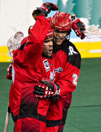 Calgary's Shawn Evans, left, and Karsen Leung celebrate Evans' goal during the Edmonton Rush's NLL lacrosse playoff game against the Calgary Roughnecks at Rexall Place in Edmonton, Alta., on Friday, May 16, 2014. Codie McLachlan/Edmonton Sun/QMI Agency