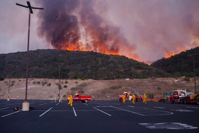 Firefighters battle a blaze in San Marcos, California May 14, 2014. More than 20 structures, including several homes, burned to the ground and thousands of people were ordered to evacuate on Wednesday, as a wind-lashed wildfire roared out of control in the heart of a Southern California coastal community. The so-called Poinsettia Fire, which erupted shortly before 11 a.m. in Carlsbad, some 25 miles north of San Diego, quickly became the most pressing battle for crews fighting flames across the region amid soaring temperatures and hot Santa Ana winds.   REUTERS/Sam Hodgson   (UNITED STATES - Tags: ENVIRONMENT DISASTER)