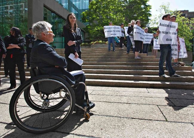 BC Civil Liberties Association says the Supreme Court of Canada will hear its case in October. Lawyers Joseph Arvay (L) and Grace Pastine (C) wait to talk to the media as members of the Euthanasia Prevention Coalition protest outside the British Columbia Supreme Court in Vancouver June 15, 2012. The court in a ruling declared a section of the Criminal Code that prohibits physician-assisted death invalid. Arvay represented plaintiff Gloria Taylor who suffered from ALS and argued the law infringes on the equality of rights. (REUTERS/ ANDY CLARK)