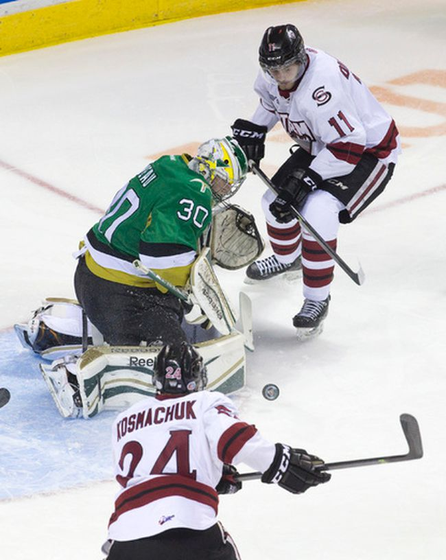 Guelph Storm forwards Jason Dickinson and Scott Kosmachuk chase down a loose puck deflected by Val d'Or Foreurs goaltender Antoine Bibeau during their 2014 Memorial Cup round robin hockey game at Budweiser Gardens in London, Ontario on Monday May 19, 2014.