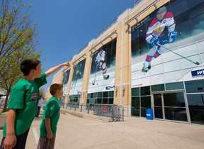 Jacob Martin, 8 and his little brother Mason, 5, look at the huge posters of the captains of the four teams playing in the Memorial Cup in London, Ont. on Monday May 19, 2014. At right is Edmonton Oil Kings' captain Griffen Reinhart. (Mike Hensen, The London Free Press)