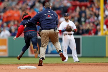 A fan is tackled by Boston Red Sox security as she runs onto the field during the ninth inning against the Toronto Blue Jays at Fenway Park on May 22.
