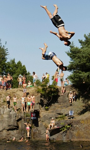 Competitors jump into the water during a cliff diving competition near the central Bohemian village of Hrimezdice August 2, 2013.  REUTERS/David W Cerny