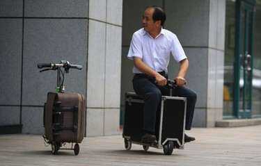 This picture taken on May 28, 2014 shows Chinese farmer He Liangcai riding a motorized scooter suitcase that he invented on the street in Changsha, central China's Hunan province. He has spent the past ten years developing this suitcase that has a top speed of up to 20km/h and the power capacity to travel up to 50-60km after one charge, according to local media. AFP PHOTO