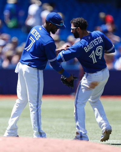 Jose Bautista hurt his leg sliding into an out at second base in the third inning and did'tt appreciate Jose Reyes touching it as Toronto Blue Jays host the Kansas City Royals in an AL game in Toronto, Ont. on Sunday June 1, 2014. Michael Peake/Toronto Sun/QMI Agency