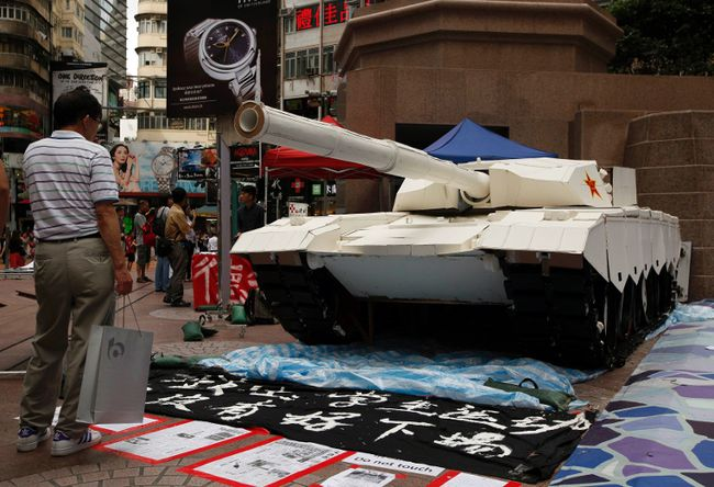 A shopper stands in front of a mock tank made by university students, imitating those used during the military crackdown on the pro-democracy movement at Beijing's Tiananmen Square in 1989, during an exhibition on the movement at Hong Kong's Causeway Bay shopping district June 3, 2014. Wednesday marks the 25th anniversary of the crackdown. (REUTERS)