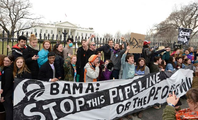 Environmentalists, many of whom have zip-tied themselves to the fence of the White House in Washington, rally and call on U.S. President Barack Obama to reject the Keystone XL pipeline in this March 2, 2014 file photo. (REUTERS/Mike Theiler/Files)