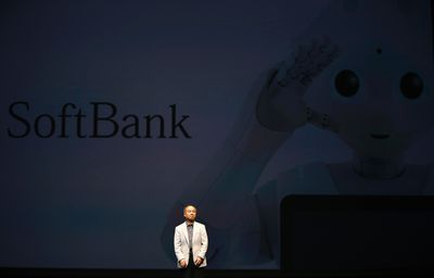 """SoftBank Corp. chief executive Masayoshi Son speaks during a news conference as huge screen showing the company's human-like robots named """"Pepper"""" in Urayasu, east of Tokyo June 5, 2014.  REUTERS/Issei Kato"""