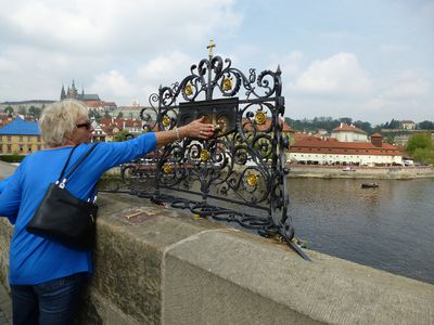 A woman touches a plaque marking the spot where St. John of Nepomuk was thrown into the Vitava River. Legend has it that touching the plaque ensures your wish will come true and you will return to Prague. ROBIN ROBINSON/TORONTO SUN