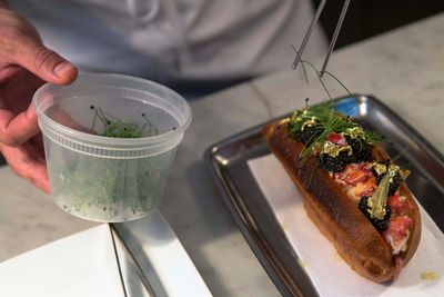 """Chef Luke Venner places chives on a gold and caviar-enriched lobster roll that sells for $160 at """"BLT Fish"""" restaurant in New York June 4, 2014. BLT Fish is a high-end fish restaurant and has a less expensive dining room two floors below, called """"BLT Shack"""", which already serves a traditional lobster roll. Venner said his inspiration for his caviar and gold-infused version was a desire to tie the two restaurant concepts together.   REUTERS/Brendan McDermid"""