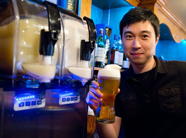 Co-owner Jimmy Lee tops a pint with frozen beer Thursday behind the bar at the Poacher's Arms on Richmond St.   (CRAIG GLOVER, The London Free Press)