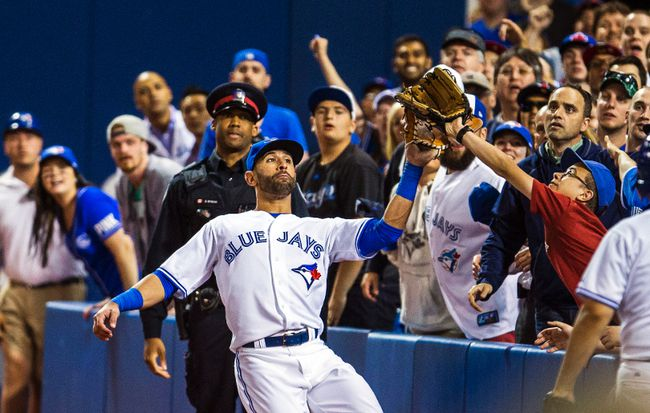 Toronto Blue Jays outfielder Jose Bautista is interfered with by a fan while tracking a pop up against the St. Louis Cardinals at the Rogers Centre in Toronto, June 6, 2014. (ERNEST DOROSZUK/QMI Agency)
