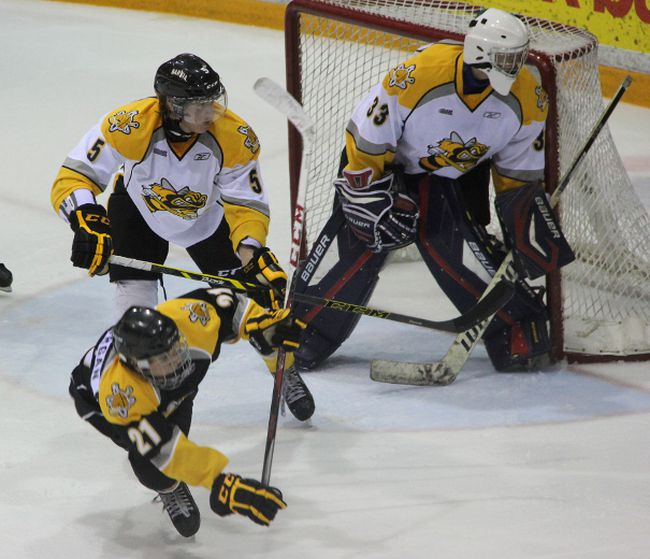 Sarnia Sting prospect, and 1st overall pick in the 2014 OHL Priority Selection, Jakob Chychrun (in white) sends Drew Morgan flying in front of the net during a scrimmage on day two of rookie camp on Sunday, June 8. The camp took place on Saturday and Sunday and was an opportunity for recent draft picks to meet and get acquainted with Sting staff. SHAUN BISSON/THE OBSERVER/QMI AGENCY