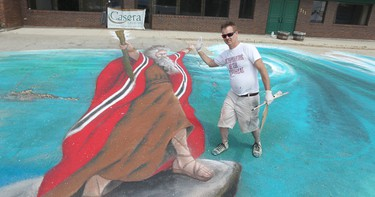 Murallist Charlie Johnston high-fives a 35-foot tall Moses in his 3D chalk art drawing of the parting of the Red Sea during the 50th edition of Transcona's Hi Neighbour Festival on Regent Avenue on Sun., June 8, 2014. Kevin King/Winnipeg Sun/QMI Agency