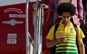 Cameroon player Benoit Assou Ekotto leaves the plane after landing in Galeao Aerial Base ahead of the World Cup in Rio de Janeiro June 9, 2014. (REUTERS/Ricardo Moraes)