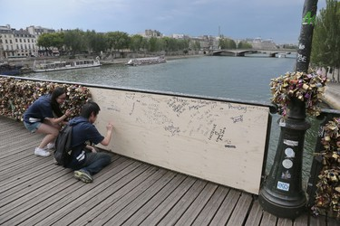 People write inscriptions onto a wooden panel on the Pont des Arts bridge over the Seine river in Paris on June 9, 2014. Thousands of 'locks of love' attached to the footbridge caused  part of the railing to collapse and temporarily replaced by a wooden board, forcing an evacuation on June 8. Thousands of lovers from across the world visit the Pont des Arts every year and seal their love by attaching a lock carrying their names to its railing and throwing the key in the Seine. The phenomenon has become something of a headache for officials in the City of Light, who would prefer something that poses fewer problems of security and aesthetics. AFP PHOTO /JACQUES DEMARTHON