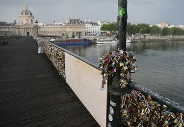 A photo taken on June 9, 2014 shows 'love padlocks' attached to a fence of the Pont des Arts bridge over the Seine river in Paris. Thousands of 'locks of love' attached to the footbridge caused  part of the railing to collapse, forcing an evacuation on June 8. Thousands of lovers from across the world visit the Pont des Arts every year and seal their love by attaching a lock carrying their names to its railing and throwing the key in the Seine. The phenomenon has become something of a headache for officials in the City of Light, who would prefer something that poses fewer problems of security and aesthetics. AFP PHOTO /JACQUES DEMARTHON