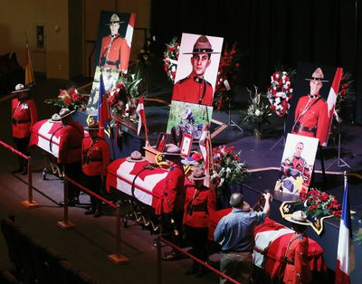 The caskets of Royal Canadian Mounted Police (RCMP) Constables Dave Joseph Ross (L) from Victoriaville, Quebec,  Douglas James Larche  (C) from Saint John, New Brunswick,and Fabrice Georges Gevaudan of Boulogne-Billancourt, France, are draped in Canadian flags for a public viewing of the Fallen Three at Wesleyan Celebration Center in Moncton, New Brunswick June 9, 2014.  A 24-year-old man was charged with murder on Friday in the slayings of three Royal Canadian Mounted Police officers during a shooting spree in the eastern Canadian city of Moncton.     REUTERS/Christinne Muschi