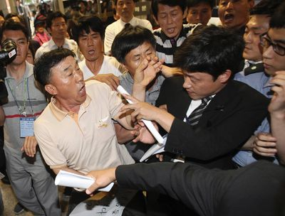 """Family members of passengers aboard the sunken ferry Sewol struggle with a security officer (R), while attempting to attend a trial of the ferry's crew members at Gwangju District Court in Gwangju June 10, 2014. Fifteen crew of a South Korean ferry that sank in April killing more than 300 people, mostly children, went on trial on Tuesday on charges ranging from negligence to homicide, with the shout going up of """"murderer"""" as the captain entered the court. REUTERS/Ahn Young-joon/Pool (SOUTH KOREA - Tags: MARITIME DISASTER CRIME LAW)"""