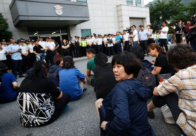 """Family members of victims onboard sunken ferry Sewol sit in front of a building in which crew members are detained, after attending a hearing at the local court in Gwangju June 10, 2014. Fifteen crew of a South Korean ferry that sank in April killing more than 300 people, most of them children, went on trial on Tuesday on charges ranging from negligence to homicide, with the shout going up of """"murderer"""" as the captain entered the court.   REUTERS/Kim Hong-Ji (SOUTH KOREA - Tags: MARITIME DISASTER TRANSPORT CRIME LAW)"""