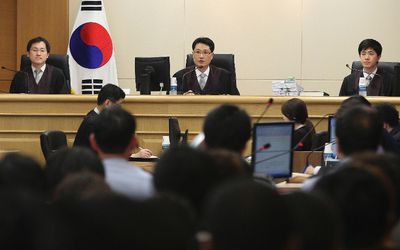 """Judges sit to preside over a trial of crew members of the sunken ferry Sewol at Gwangju District Court in Gwangju June 10, 2014. Fifteen crew of a South Korean ferry that sank in April killing more than 300 people, mostly children, went on trial on Tuesday on charges ranging from negligence to homicide, with the shout going up of """"murderer"""" as the captain entered the court. REUTERS/Ahn Young-joon/Pool"""