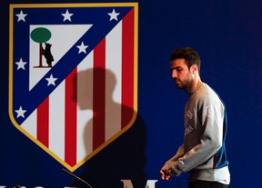 Cesc Fabregas walks in front of an Atletico Madrid coat of arms before a news conference at the Vicente Calderon stadium in Madrid, April 8, 2014. (REUTERS/Paul Hanna)