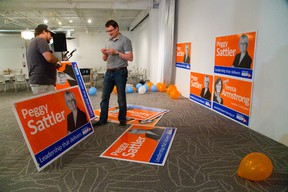 Rob Spencer and Joshua Randall start putting up election posters of their London area MPP's Peggy Sattler and Teresa Armstrong at the NDP election night headquarters at the GoodWill building on Horton in London, Ont. on Thursday June 12, 2014.  Mike Hensen/The London Free Press/QMI Agency