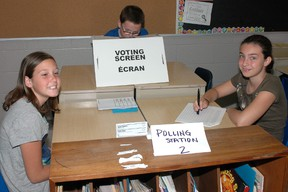 While Dillon Crossett, centre, voted Wednesday at Locke's Public School, polling clerks Amanda Wilcox, left, and Leyla Boyacigil took care of the paperwork.