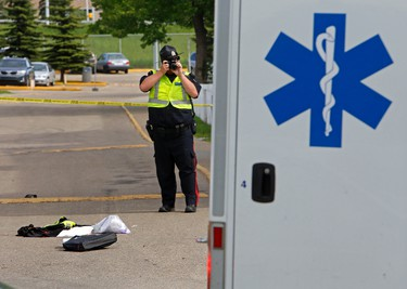 Edmonton Police Service member investigates after a 33-year-old man was killed when he tried to stop another man from stealing his pick-up truck at the Parkridge Estates at 2908-116A Avenue in Edmonton, Alta., on Friday 13, 2014. Tom Braid/Edmonton Sun/QMI Agency