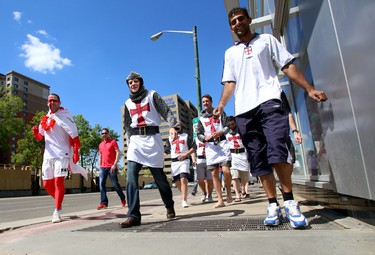A group of English soccer fans, decked out in Knights Templar costumes, walk down Jasper Avenue en route to the Pint on Whyte Avenue pub in Edmonton, AB  before the England vs. Italy World Cup match on Saturday, June 14, 2014. Trevor Robb/Edmonton Sun/QMI Agency
