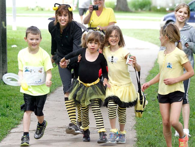Six-year-old Sophie Hamza is cheered on by friends and family members as she nears the finish line at Upper Queen's Park during the Strides for Sophie family fun run in Stratford. The event was held to raise funds and awareness about a rare genetic disorder called Sanfilippo Syndrome. (MIKE BEITZ/The Beacon Herald file photo)
