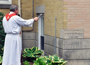 Fr. Moe Charbonneau (left), former Pastor of St. Patrick's Parish in Dublin, gave the commemorative blessing of the office cornerstone. Fr. Charbonneau was a surprise guest who con-celebrated the anniversary service. ANDY BADER/MITCHELL ADVOCATE