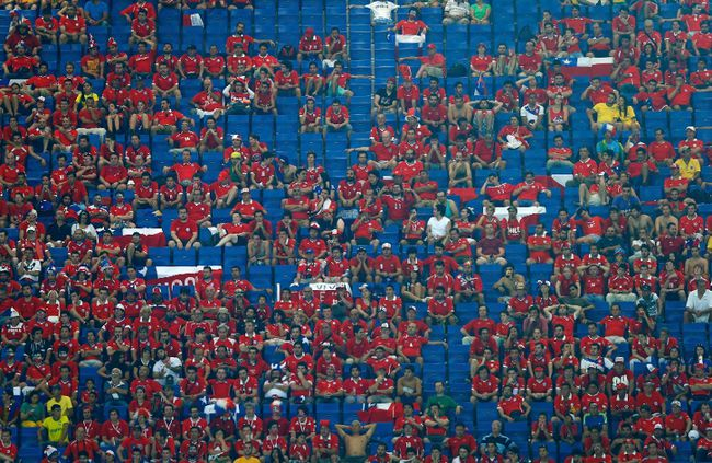 Fans are surrounded by empty seats during the World Cup match between Chile and Australia at the Pantanal arena in Cuiaba June 13, 2014. (REUTERS/Eddie Keogh)