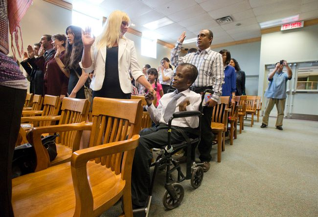 Haitian native John Espoir holds his adoptive mother Tanya Bultje's hand as he takes the Oath of Citizenship at the Citizenship and Immigration Canada office on Exeter Road in London, Ontario on Wednesday June 18, 2014.  Espoir, who was given up for dead as an infant born with encephalitis, was adopted by the Londoner who discovered the boy in an orphanage.  