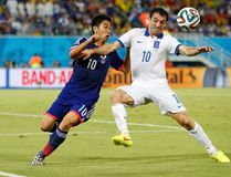 Japan's Shinji Kagawa (L) fights for the ball with Greece's Giorgos Karagounis during their 2014 World Cup Group C soccer match at the Dunas arena in Natal June 19, 2014. (REUTERS/Toru Hanai)