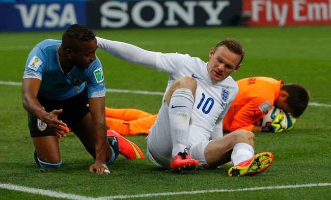 England's Wayne Rooney (middle) hits the ground next to Uruguay's Alvaro Pereira after missing a chance to score during the World Cup match at the Corinthians arena in Sao Paulo June 19, 2014. (REUTERS/Laszlo Balogh)