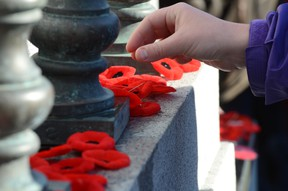Poppies are left at the Cenotaph in Central Memorial Park in Calgary in this November 11, 2013 file photo. (Stuart Dryden/QMI Agency)
