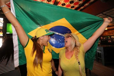 Evelyn Bertollo (l) and Willow Beatch holds the Brazil flag after Brazil scored their second goal against Cameroon in World Cup action during the first half.  Hundreds of Brazilian fans gather at the Pint in downtown Edmonton, Alta., on Monday, June 23, 2014.  Perry Mah/Edmonton Sun/QMI Agency